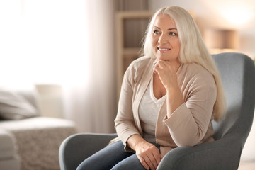 Portrait of beautiful mature woman sitting in armchair at home