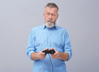 Emotional senior man playing video game on grey background
