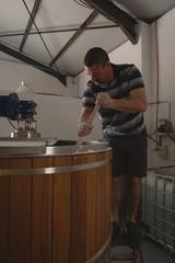 Male worker stirring gin in distillery