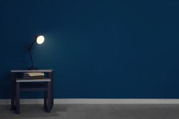 Lamp on table in dark room