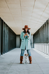 Young beautiful woman using her cellphone outdoors playing with her cute and sweet dog. Beautiful brickbackground. Lifestyle photography