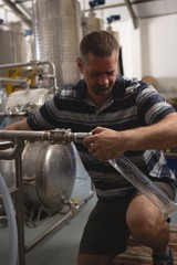 Male worker filling gin in measuring cylinder from distillery