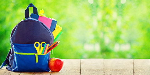 Banner. Full School backpack with apple on wooden and nature green background.