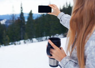 Girl standing with her back on the background of mountains in the hands of a glass and with her second hand making a selfie on the phone