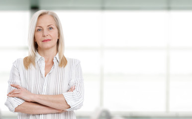 Attractive middle aged business woman with folded arms.
