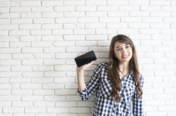 Happy millennial girl having fun indoors. Portrait of young beautiful woman with perfect teeth smile, brown eyes. Minimalistic interior, white brick textured wall background, loft style. Copy space.