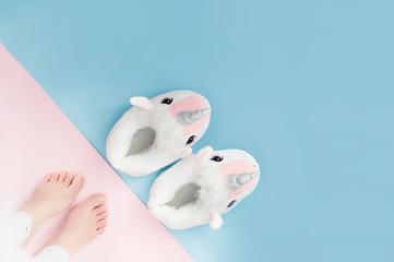 pop art pair of fluffy white unicorn slippers on pastel colour background
