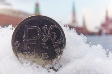 A coin worth one Russian ruble against the background of the Red Square and the Moscow Kremlin.