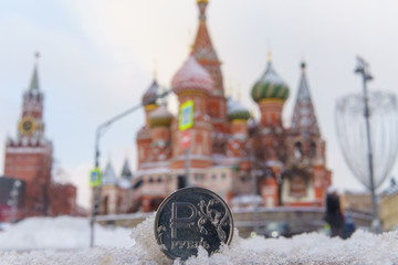 A coin worth one Russian ruble against the background of St. Basil's Cathedral in Moscow.