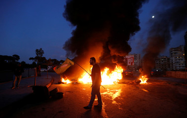 A supporter of Amal movement holds the party's flag near burning tires in Beirut