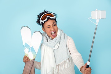 Young african woman isolated on blue wall studio winter sport skiing taking pictures