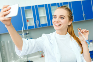 Young chemistry teacher in school laboratory work standing selfie photos