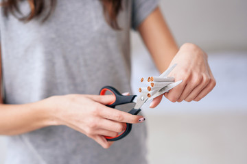 Concept of health protection. Quit smoking, health care concept. No smoking. Close up of female hands holding bunch of cigarettes and cutting them in halves with ccissors. Stop smoking concept.