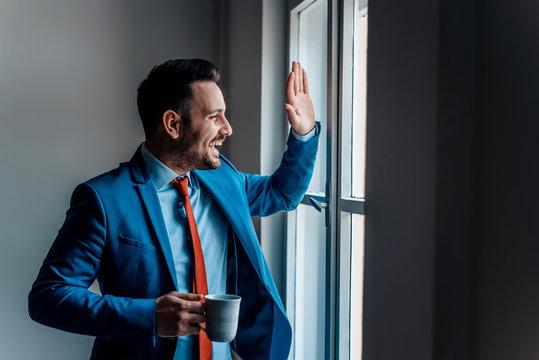 Smiling businessman greeting friend through window.