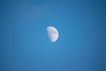 Blue moon on the light blue day sky