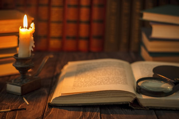 On the wooden background of the table there are stacks of colorful books near the old candlestick with burnt matches lying next to each other.