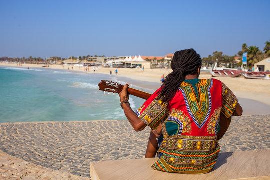 Musician with guitar and rasta hair at Santa Maria Beach, Sal, Cape Verde