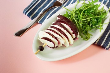 Baked beetroot with cheese, rucola, closeup.