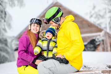 Happy family with baby boy in winter spots clothes sitting on the bench outdoors during the winter vacations