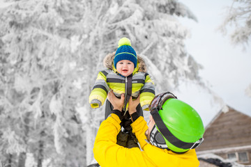 Happy father playing with baby boy standing in winter spots clothes outdoors during the winter vacations