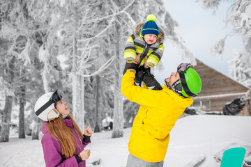 Happy family playing with baby boy standing in winter spots clothes outdoors during the winter vacations