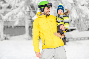 Portrait of a happy father with baby boy standing in winter spots clothes outdoors during the winter vacations