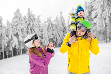 Portrait of a happy family playing with baby boy during the winter vacations on the beautiful mountains with snow-covered forest on the background