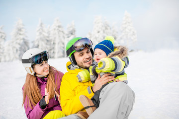 Portrait of a happy family with baby boy during the winter vacations on the beautiful snow-covered mountains