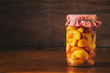 Preserved fruit in jar, compote of peaches. Homemade conserved fruits in glass on a wooden table.