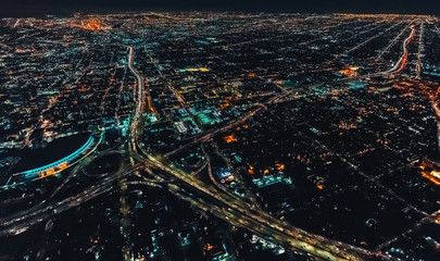 Aerial view of a massive highway in Los Angeles, CA at night with young woman holding out a smartphone in her hand Fototapete