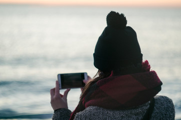 Tourist woman holding smart phone taking photo while standing backside watching at beautiful sea