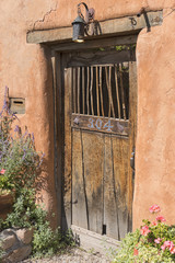 Adobe Style Architecture Old Faded Wooden Door with Lantern
