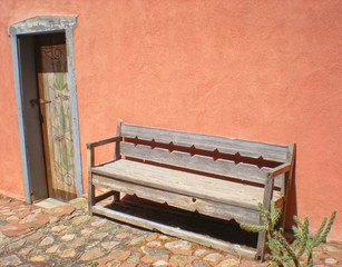 Southwest Rustic Wooden Bench Against Orange Adobe Wall
