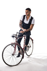 Portrait of young tattooed man in elegant clothes and shoes riding a bicycle. Studio shot. Full body shot