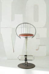 a high metal chair against a background of huge letters