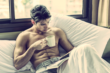 Sexy handsome young man laying shirtless on his bed next to window, holding a coffee or tea cup while reading a book