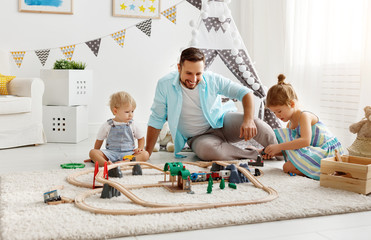 family father and children play a toy railway in   playroom