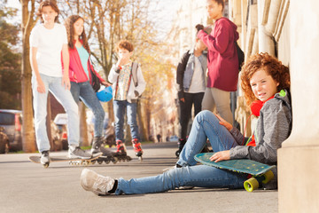 Teenage boy sitting on sidewalk with skateboard