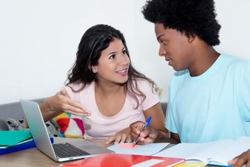 Studentin hilft afrikanischem Studenten beim Lernen