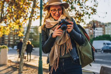 Sunny day, autumn.Young woman tourist, photographer, hipster girl dressed in hat and eyeglasses,sits on bench on city street and takes photo.Vacation, travel,adventure, sightseeing.Blurred background.