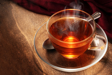 Foto op Plexiglas Thee black tea freshly brewed in a glass cup, steaming hot drink on dark rustic wood, copy space