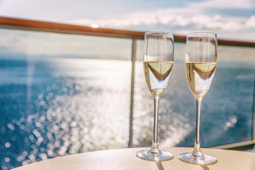 Luxury cruise ship travel champagne glasses on balcony deck with ocean sunset view on Caribbean vacation. Drinks in sun flare on cruise holiday destination.