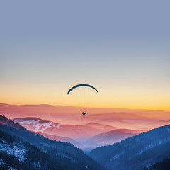 Photo sur Toile Aerien Parachuting in sunset light above mountains