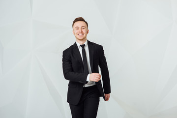 Cheerful young businessman in black suit