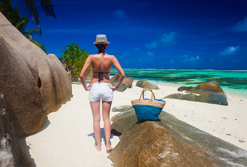 back view of fit young woman relaxing between the rocks of Anse Source d Argent. La Digue island, Seychelles