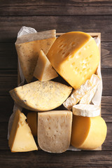 Different kinds of cheese in crate on wooden background, top view