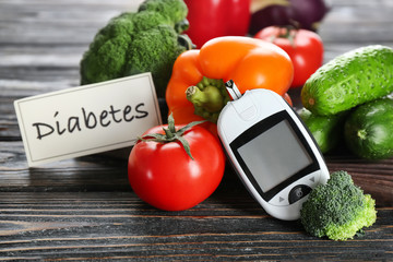 Digital glucometer and vegetables on table. Diabetes diet