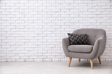 Comfortable armchair near white brick wall