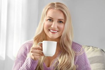 Mature smiling woman drinking tea indoors