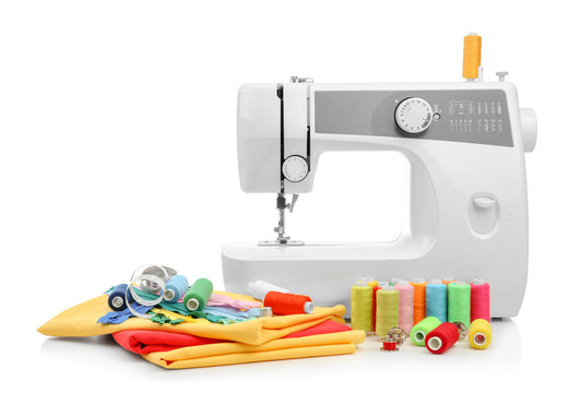Modern sewing machine with threads and fabrics on white background